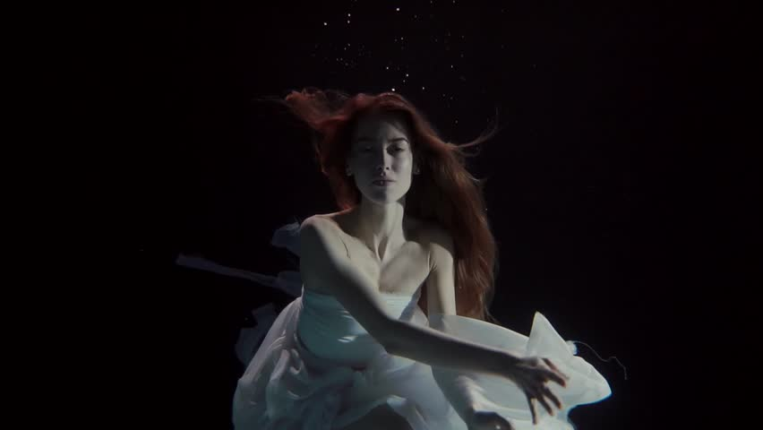 young woman swimming underwater in a white dress like a fairy tale