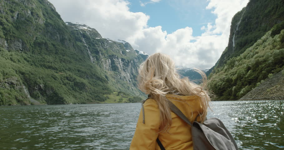 Woman sitting in boat on Fjord Norway hair blowing in wind traveling towards scenic landscape nature background view enjoying vacation travel adventure | Shutterstock HD Video #25058723