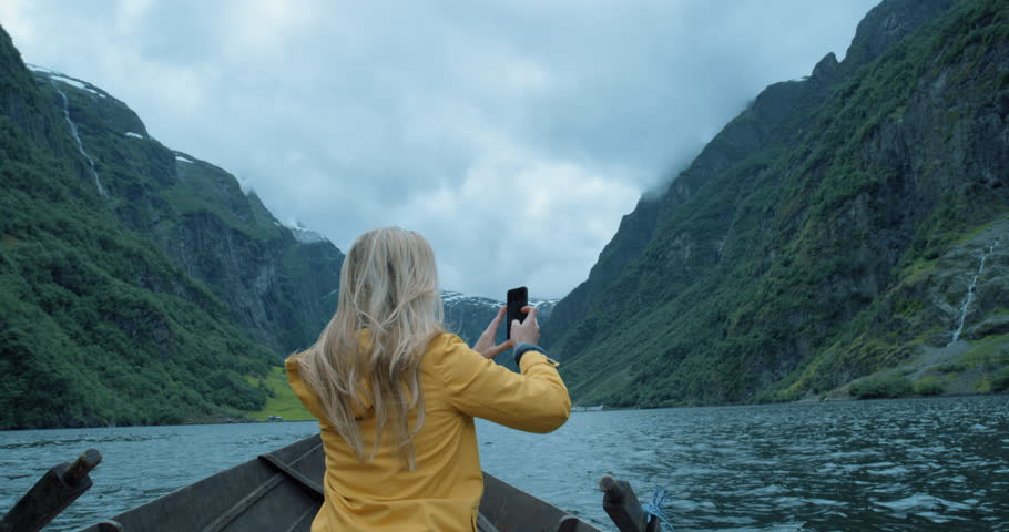 Brave Woman taking photograph in stormy weather on Fjord Norway with smartphone photographing scenic landscape nature background view enjoying vacation travel adventure | Shutterstock HD Video #25058843