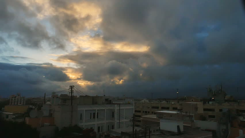 Darkness over roof tops old town San Juan, Puerto Rico as first light of day highlights the rapidly blowing clouds | Shutterstock HD Video #25062107