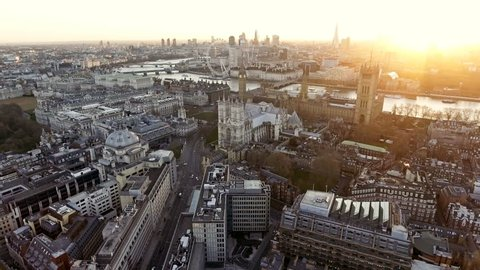 Panoramic Aerial Shot of Houses of Parliament & Big Ben in Central London features The London Eye Wheel, River Thames and Iconic Business Buildings Skycrapers with Beautiful Sunrise 4K