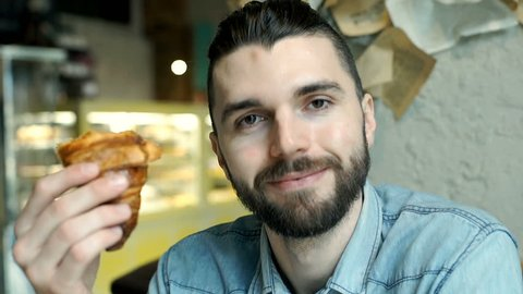 Handsome man looks happy while eating tasty croissant in the cafe