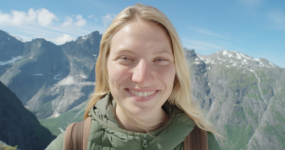 Close up portrait of Woman Climber smiling at top of mountain in nature with blonde hair blowing in wind above the clouds view Hiker Girl trekking in Norway Slow Motion #25088513