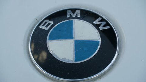 The blue white and black logo of BMW car on the carshow along with the other cars displayed