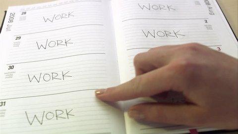 A hand browsing through an agenda.