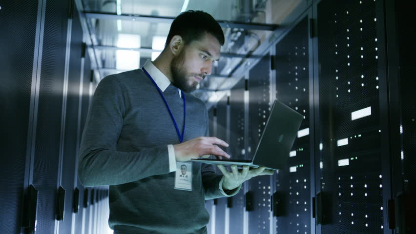 IT Technician Works on Laptop in Big Data Center full of Rack Servers. He Runs Diagnostics and Maintenance. Shot on RED EPIC-W 8K Helium Cinema Camera.