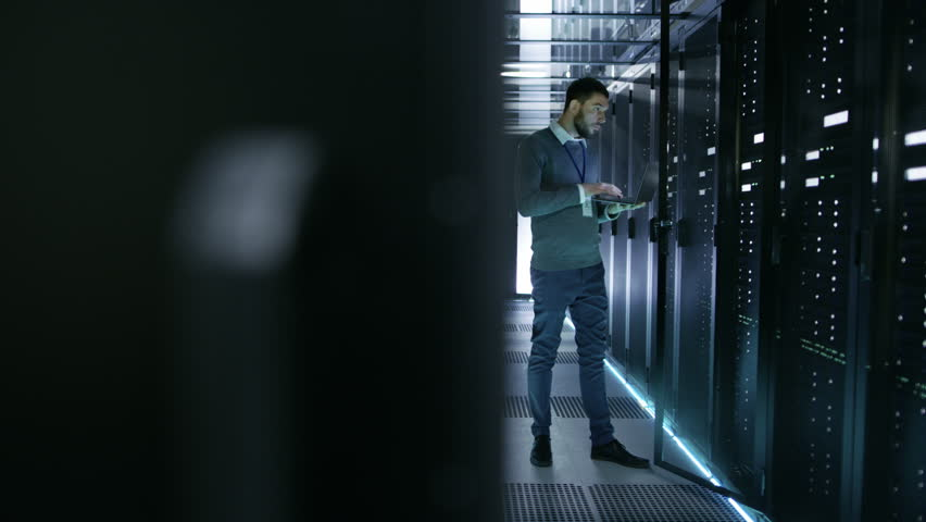 IT Technician Works on Laptop in Big Data Center full of Rack Servers. He Runs Diagnostics and Maintenance, Sets System Up. Shot on RED EPIC-W 8K Helium Cinema Camera.