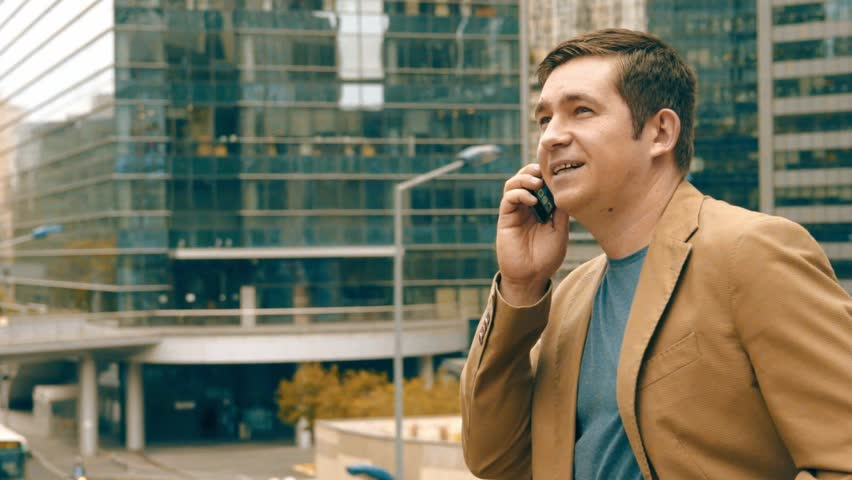Bisiness person talking on the phone around modern business buildings at summer day.  | Shutterstock HD Video #25122053