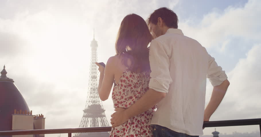Tourist couple taking photograph of Eiffel Tower using smartphone hotel balcony at sunrise photographing scenic Paris cityscape background view enjoying European honeymoon vacation travel adventure | Shutterstock HD Video #25124573