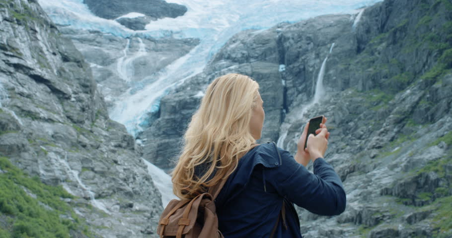 Brave explorer Woman taking panorama photograph of melting glacier with smartphone photographing Climate change concept landscape nature background view enjoying vacation travel trekking adventure | Shutterstock HD Video #25126943