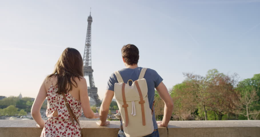 Young couple holding hands woman leading boyfriend walking towards Eiffel Tower Paris POV travel concept