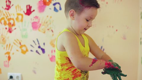 Close up veiw of cute little boy with painted hands after leaving his colorful handprints on the wall and showing his thumb up. Young happy family. Mother and child concept