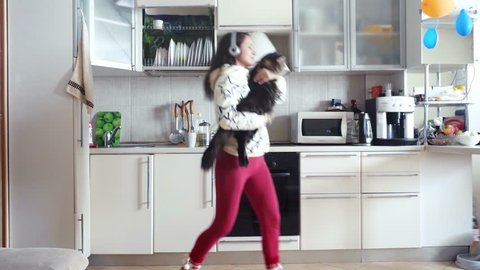Joyful young beautiful woman is dancing in kitchen with her adorable Maine Coon cat wearing headphones in the morning listening to music on smartphone. 3840x2160