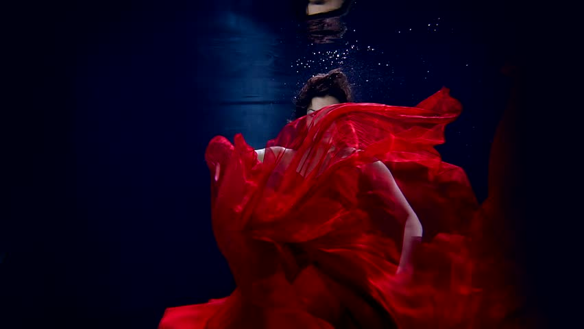 Flight in weightlessness of the underwater world of the young beautiful girl in elegant red dress.