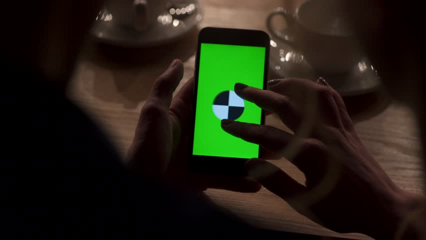 Close up view of woman's hand zooming the picture on the greenscreen/phone, man's hand holding the mobile phone. Café surroundings, wooden table. Women presenting smth on the device. #25145243