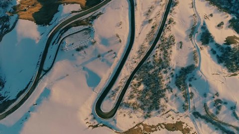 Aerial view of winding mountain road. Film intro. Sunset in the snow-capped mountains. Majestic mountains. Beautiful Russia. Winter sunset over road.