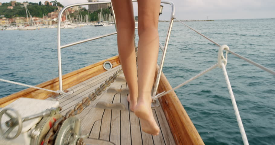 Beautiful woman on sailboat in bikini following legs feet on luxury summer lifestyle happy adventure travel vacation