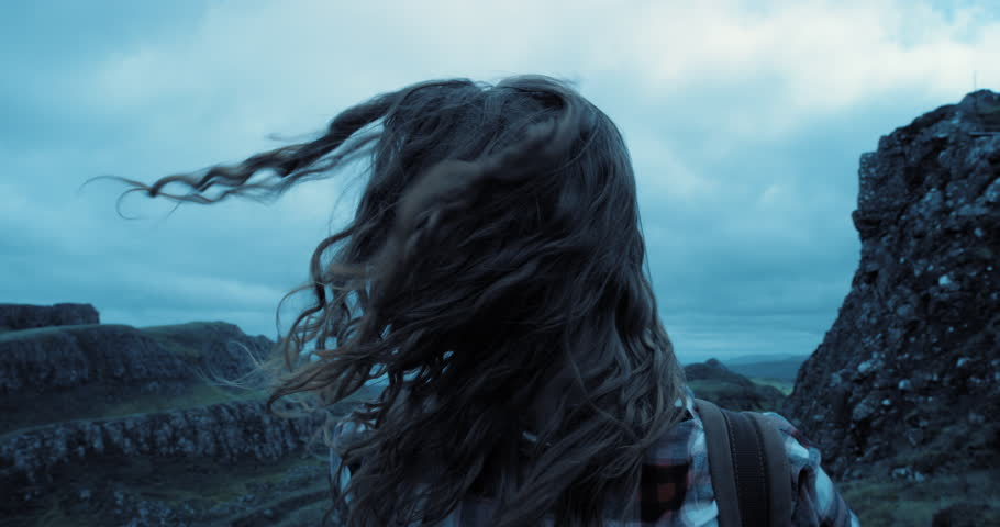 Close up portrait of Young Woman hiker exploring nature with hair blowing in wind Hiker Girl trekking in cold stormy weather Quiraing Scotland Slow Motion