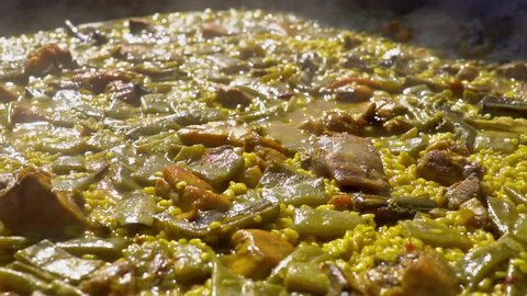 Cooking authentic Valencian paella with chicken meat, rabbit meat, vegetables, boiling Valencian rice, saffron. Typical cuisine of the Valencia Spain. Boiled bubbles in slow motion