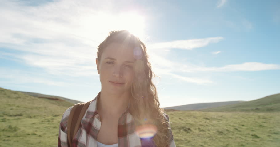 Close up portrait of Beautiful Young Woman Smiling in nature with hair blowing in wind Hiker Girl standing in front of sun flare trekking in Scotland Slow Motion