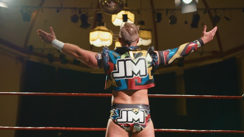 Portrait of Pro Wrestler with Arms Raised, Posing in Ring before Wrestling Match (slow motion)