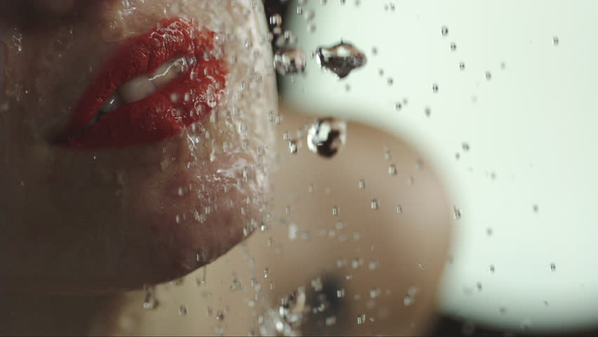 Woman taking a shower in slow motion. beautiful girl with lipstick under a shower enjoying. mouth  and lips close up