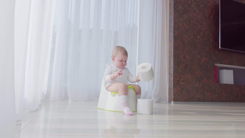 Small child sits on the potty and relieves itself