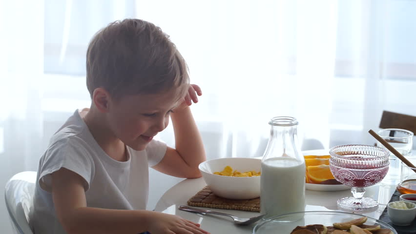 boy pouring milk into a bowl of corn flakes. The boy is cooking Breakfast