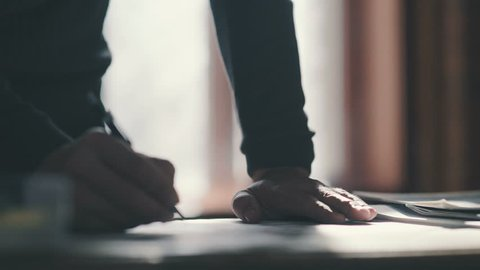 Close-up: the man bends over the desk and makes notes with a pen, leaning on the table. Close-up: a writing pen. The man's hand holds the pen and guides the line along the paper.