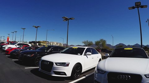 SCOTTSDALE AZ/USA: February 28, 2017- Car view driving by used expensive luxury and sports cars at a Scottsdale Arizona dealership. A row of pricey cars are on display in pre-owned car lot.
