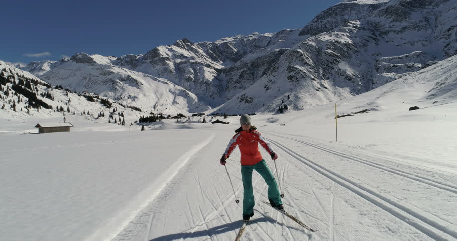 Cross-country skiing in mountains. Skate skiing on groomed track. Aerial view