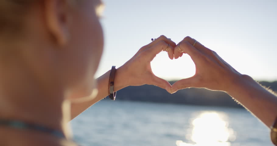 Close up of attractive woman hands making heart shape gesture at sunset golden light flares shining through on empty beautiful beach | Shutterstock HD Video #25246103