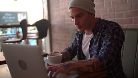Cool young hipster drinking cappuccino, searching online on his computer in hip coffee shop