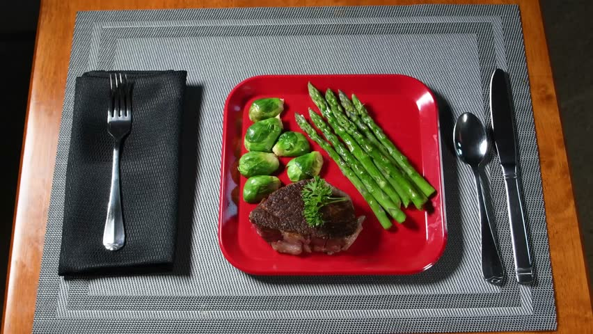 A low-carbohydrate meal of steak, brussels sprouts and asparagus is served on a red plate, which is placed on a gray place mat