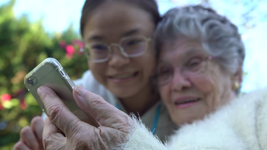 4K Smiling asian granddaughter showing and teaching mobile phone to her grandmother. Happy family, grandchild and grandma using and looking at smart phone in the garden house-Dan
