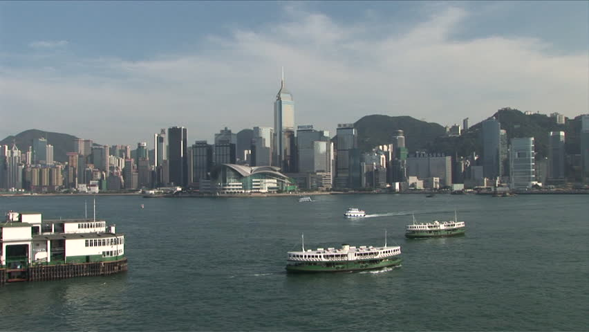 Hong Kong, China - CIRCA April, 2007: Wide shot of the skyline and the Star Ferry terminal as seen from the water's edge of the harbor during the day #2531123