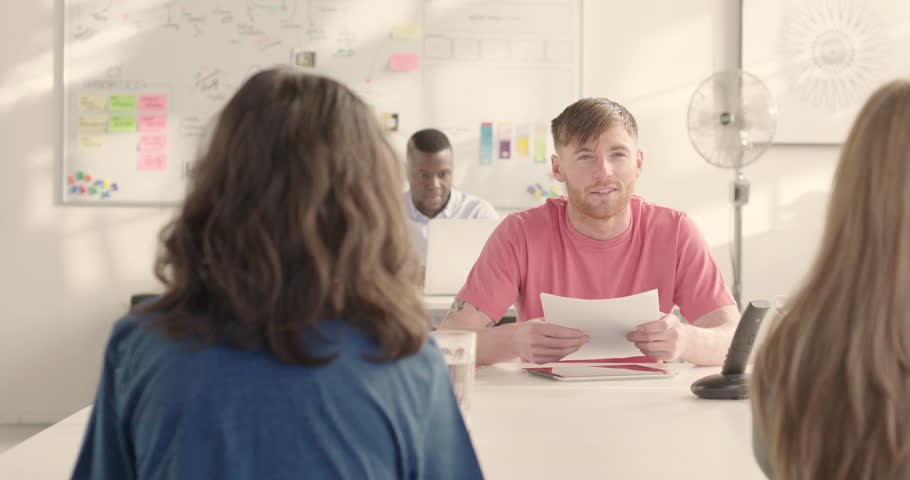 Young casual man leads meeting at conference table in sunny startup office track. Raw option available on request | Shutterstock HD Video #25328363
