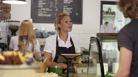 4K Cheerful worker serving customers & taking payment in city coffee shop