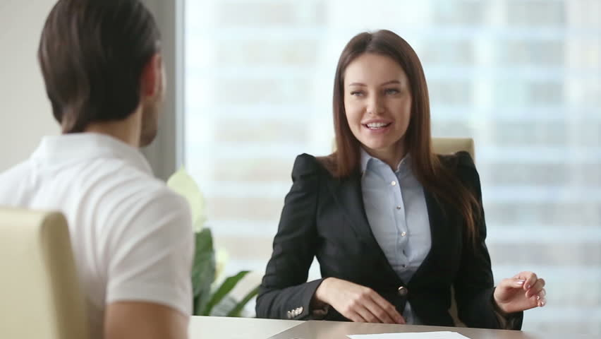 Young happy beautiful businesswoman consultant wearing formal suit meeting casual client at modern office. Two colleagues or partners negotiating, working with documents. Young man reading contract
