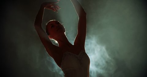 graceful ballerina dancing elements of classical ballet in the dark with light and smoke on the background, slow motion