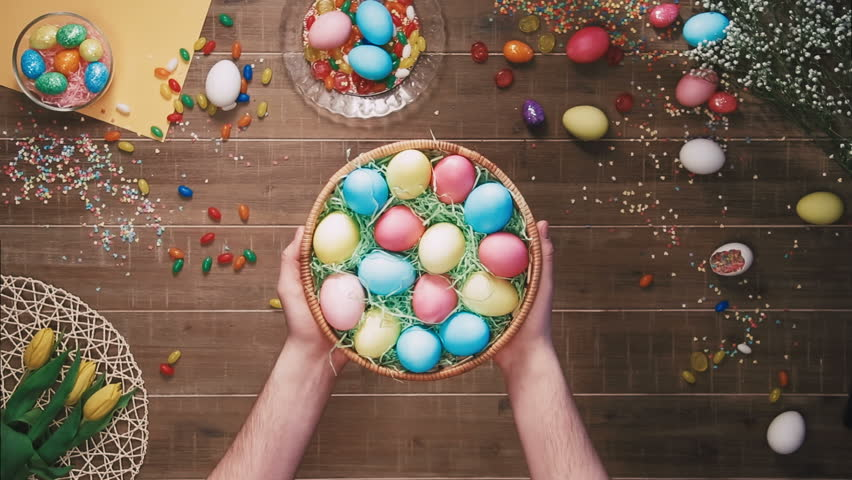Man holding a basket with easter eggs in front of table decorated with easter eggs. Top view   Shutterstock HD Video #25342943