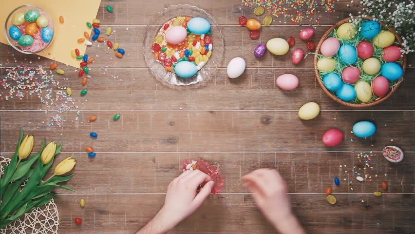 Man putting candys in the bag on table decorated with easter eggs. Top view | Shutterstock HD Video #25343003