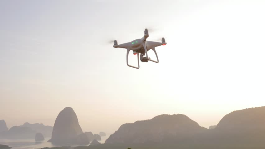 Quadcopter Drone Taking Off in Park at Amazing Sunrise with Mountains on Background. Phuket, Thailand. HD.