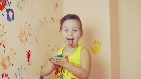 Little boy in yellow sleeveless shirt showing tongue. His hands are dirty in colors. He is living his handprints on the wall. Slowmotion