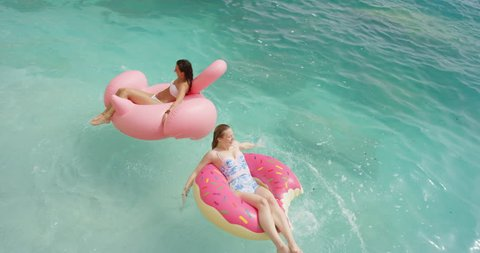Two girls lying on inflatable flamingo Best friends having fun relaxing floating in clear blue ocean Happy Women enjoying summer vacation on tropical island holiday.