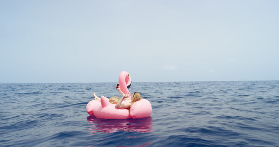 Woman lying on pink inflatable flamingo taking selfie photograph floating alone in middle of ocean