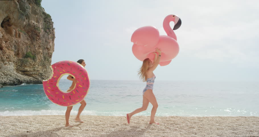 Two women walking on empty beach holding giant inflatable flamingo and doughnut Best friend girls enjoying summer vacation on tropical beach holiday
