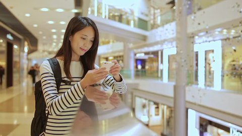 Young Woman use of mobile phone in shopping mall