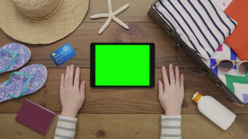 Aerial lockdown footage of woman touching digital tablet with green screen on wooden table. Overhead flat lay of beach supplies with passport and credit card on wood. Female is packing for vacation.