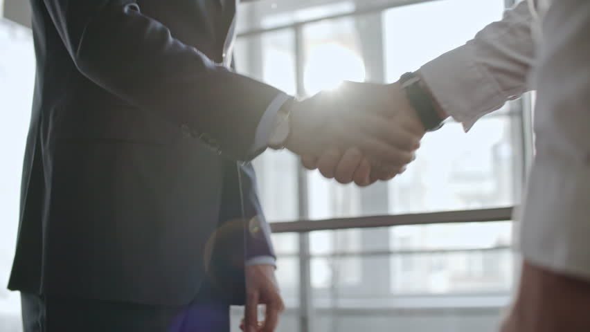 Low angle shot with tilt up of two businessmen in official clothes greeting each other with handshake and discussing work before big window
